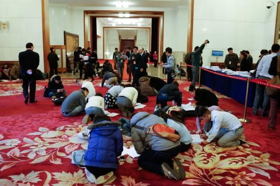 这是记者在人民大会堂内领到相关文件后抓紧阅读。新华社记者 吕迅 摄