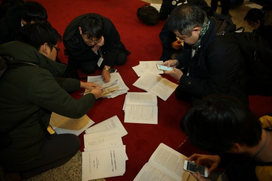这是记者在人民大会堂内领到相关文件后抓紧阅读。新华社记者陈建力摄