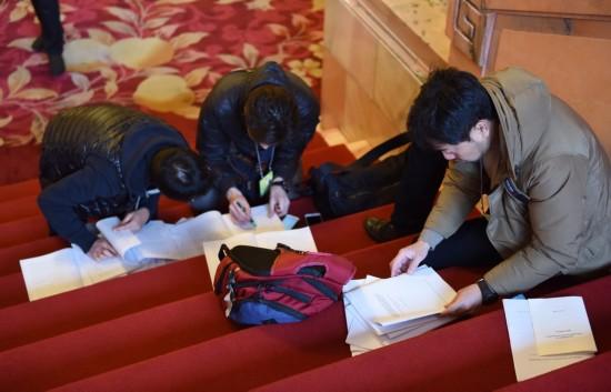 这是记者在人民大会堂内领到相关文件后抓紧阅读。新华社记者薛玉斌摄