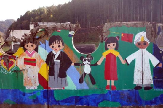 采访大川小学校。至今还孤零零站立在学校的毕业生壁画,在中国国旗之下日本人与中国人牵着熊猫的壁画