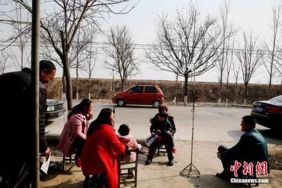 12日,山西省运城市盐湖区,民众为躲避地震在诊所外输液.   摄-山