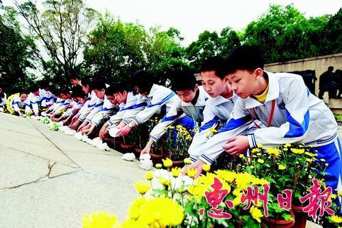 在市区丰山公园东江人民革命烈士纪念碑前,一群学生在向烈士献花。 本报记者钟畅新 摄