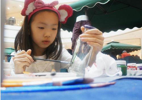 小朋友在环保DIY手工区动手做小摆件。