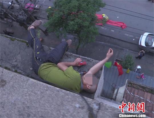 醉酒男子双脚悬空酣睡于楼顶消防员救人(图)