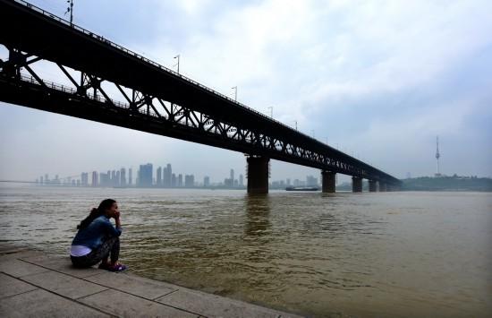 4月25日,一位市民在武汉长江在桥下江边观景。新华社记者 程敏 摄