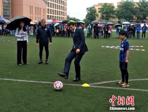 萨内蒂雨中与孩儿踢球。<a target=