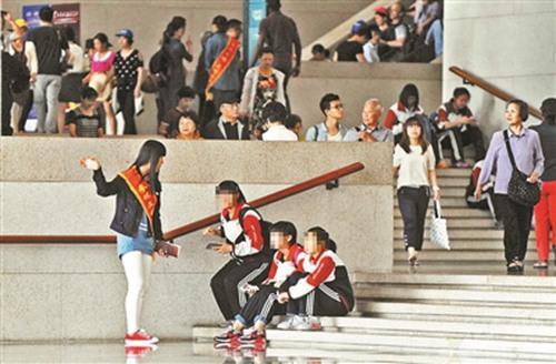 2014年5月份,博物馆内,文明引导员劝游客不要坐在台阶上。摄影:记者袁艺 图片来源:北京青年报