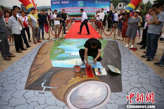 画师在描绘大水缸旁3D画。 王中举 摄