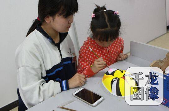 市民小朋友学习绘制脸谱。千龙网记者崔艳爽摄