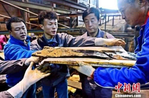 """5月19日,海昏侯墓考古发掘项目领队杨军表示,这件文物此前曾被认为是""""屏风"""",但现在看来是""""衣镜""""。图为该""""衣镜""""出土场景。 郭晶 摄"""