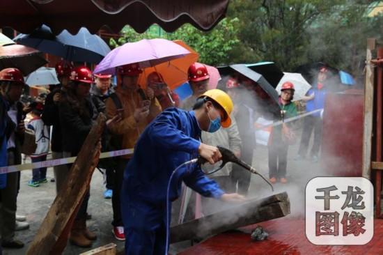 """5月14日国企开放日,在北海公园""""西天梵境""""古建修复施工现场,北京房地集团首华建设公司技术人员现场演示对木结构进行蒸汽清洗。千龙网记者包萌摄"""