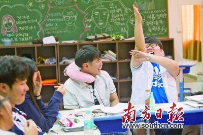 高三学生�y..�.��(N�_韩国学生高三班的上课氛围比较轻松活跃,图为一名学生搞怪举手回答