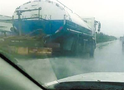 洒水车雨中洒水。网络截图