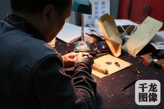 张国维的作业室位于琉璃厂的一间平房里,一盏老台灯、几方印章、几把刻刀,摆设十分简略。千龙网记者 马文娟 摄