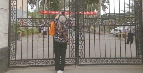 7日上午开考后,已经看不到孙子的李桂荣迟迟不愿离开,她想拍下考场内的照片,以作留念。本报记者魏新丽摄