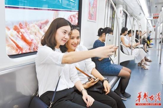 6月28日中午,长沙地铁1号线列车上,周女士(左)和同事用手机拍照。她们在马厂上班,地铁1号线开通后,她们乘车去市中心逛街购物更加方便。当天,长沙地铁1号线正式开通试运营。湖南日报记者田超摄