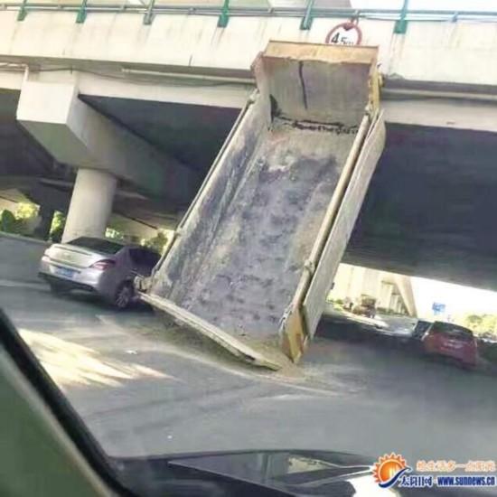 土方车行驶时车斗被卡桥底 车头飙出几十米远