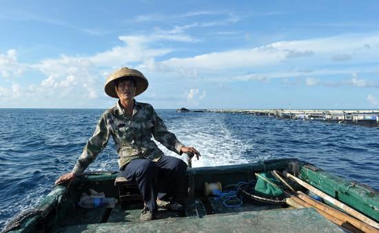 7月17日,在南沙美济礁礁盘附近,渔民施任平驾驶渔船前往深海养殖基地。