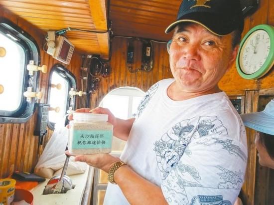 满吉胜号船长陈富盛拿出从太平岛带回来的沙