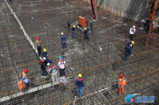 7月31日21时,沪通长江大桥28号主塔墩承台开始浇筑。这标志着世界最大桥梁沉井基础施工进入崭新阶段。   沪通长江大桥是世界上首座主跨超千米级的公铁两用斜拉桥,大桥全长11072米。大桥主塔墩承台堪称世界超级承台,面积约4673平方米,整个承台将消耗钢筋4600余吨,混凝土浇筑总方量约为41700余立方米。28号主塔墩承台将分三次浇筑,施工周期约两个月。   中铁大桥局组织450名施工人员在28号主塔墩打响施工攻坚战,他们采取多种有效措施,确保完成施工节点目标。