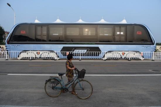 8月2日,一位市民从正在进行路面测试的巴铁1号试验车旁经过。 新华社记者 罗晓光 摄