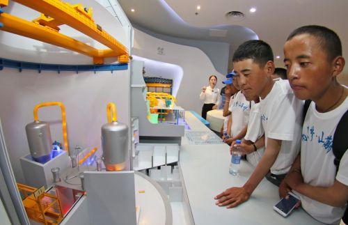 8月7日,来自西藏聂拉木县的藏族学生在山东核电科技馆观看核岛机组模型。新华社发(唐克 摄)
