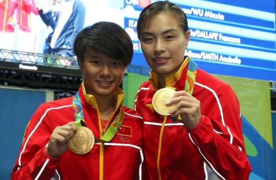 8月7日,吴敏霞(左)和施廷懋在比赛最后一跳后拥抱庆祝。当日,在2016年里约奥运会女子双人三米板决赛中,中国选手吴敏霞和施廷懋以345.60分的总成绩夺得冠军。