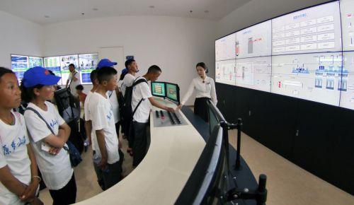 8月7日,来自西藏聂拉木县的藏族学生在山东核电科技馆了解核电运行控制。新华社发(唐克 摄)
