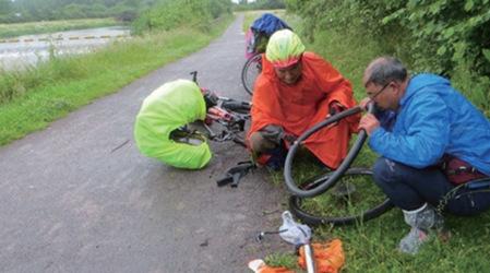 三位长者在路边维修爆胎的自行车。(《欧洲时报》/受访者供图)