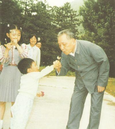 1987年4月,邓小平在北京玉泉山和孙子一起吹蒲公英图片