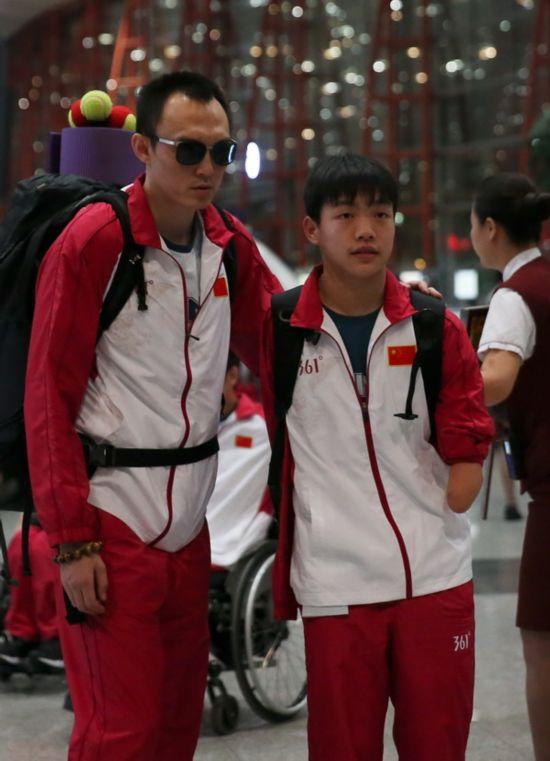 8月30日,游泳运动员杨博尊(左)与队友在机场等待出发。 新华社记者曹灿摄