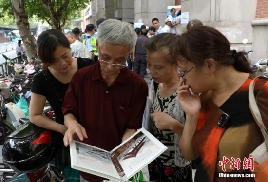 """资料图:几位杭州市民欣赏已买到的""""G20杭州峰会明信片""""。 中新社记者 王刚 摄"""