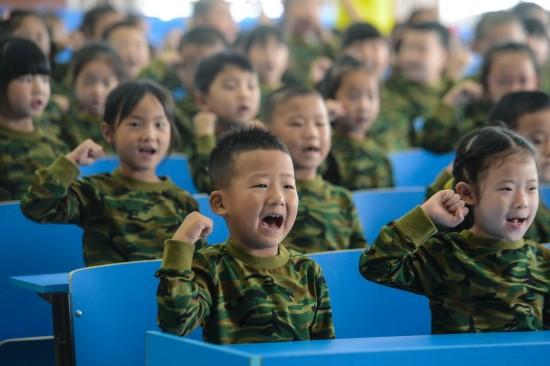"""9月7日,幼儿园的孩子们在""""娃娃军校""""开班仪式上宣读誓词""""我是小小兵,不怕困难我能行""""。  新华社记者 徐昱 摄"""