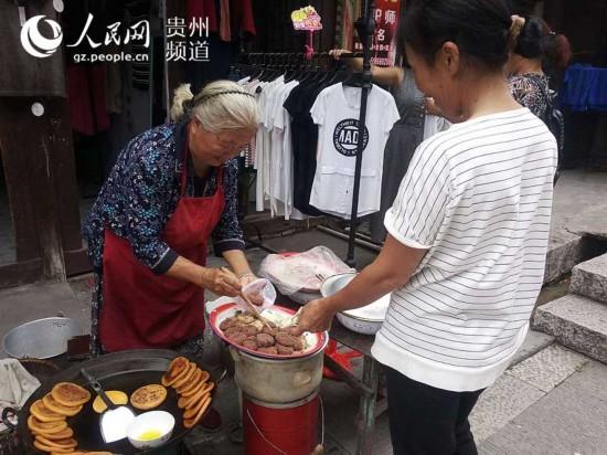 图为游客向徐业梅买当地小吃。王钦摄