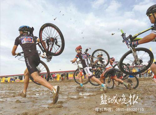 盐城大丰举办山地自行车赛 选手扛车冲刺