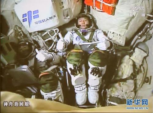 10月19日凌晨,神舟十一号飞船与天宫二号自动交会对接成功。这是两名航天员景海鹏(右)和陈冬在完成对接后竖起大拇指相互祝贺(摄于北京航天飞行控制中心大屏幕)。新华社记者 琚振华 摄 新华网