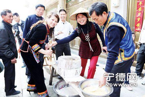 """身着华丽畲族服饰的畲家女热情邀请""""二月二""""嘉宾一同磨豆浆做豆腐。"""