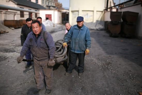 11月29日,几名留守矿工在运送井下整理出的电缆。