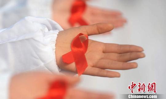 图为大学生展示防艾标志红丝带。 孟德龙 摄