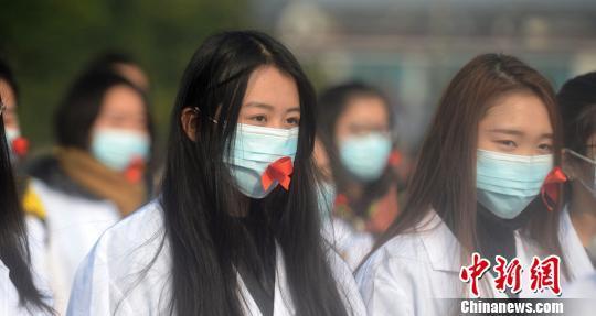 图为大学生们戴粘有红丝带的口罩。 孟德龙 摄