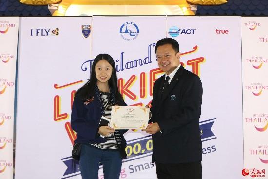 """泰国国家旅游局局长育他萨向第3000万名游客颁发""""泰国最幸运游客""""证书。"""