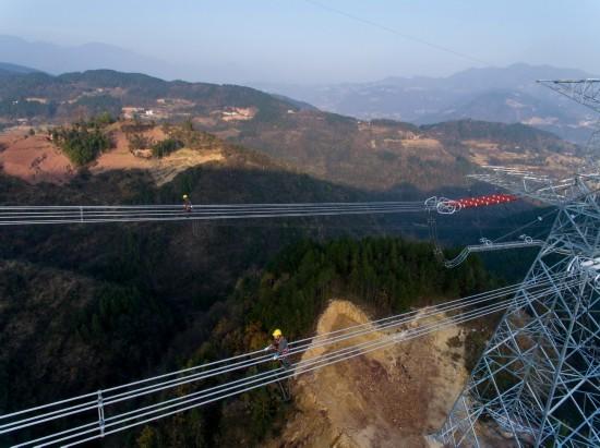 12月6日,国网重庆电力检修公司的技术人员在高空进行特高压线路验收。  新华社记者 刘潺 摄