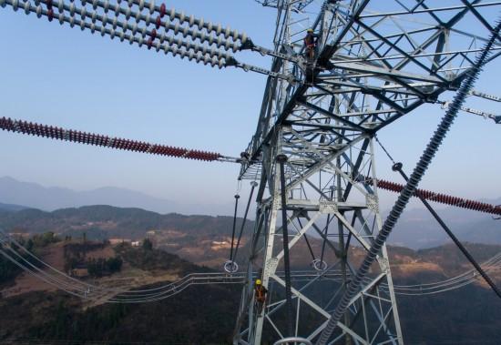 12月6日,国网重庆电力检修公司的技术人员在高空进行特高压线路塔基验收。 新华社记者 刘潺 摄