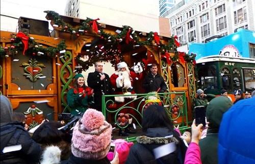 中国侨网市长伟殊(乘车者右一)乘坐梅西圣诞列车到华埠,为华埠圣诞树点灯,雪花般的纸片从天而降。(美国《世界日报》/唐嘉丽 摄)
