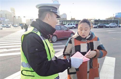 城区交通大整治期间,执勤民警向市民发放交通安全宣传单。张立芳 摄