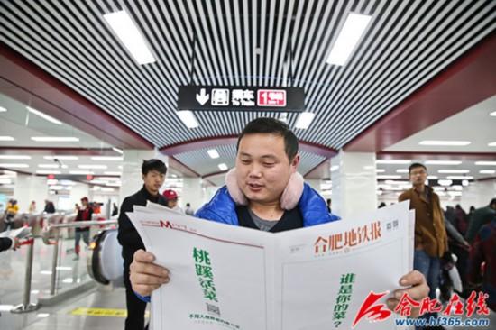 12月26日合肥地铁开通当天,一位市民正在阅读《合肥地铁报》 李福凯/摄