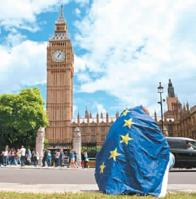 一名抗议者身披欧盟旗帜坐在英国首都伦敦街头.图片