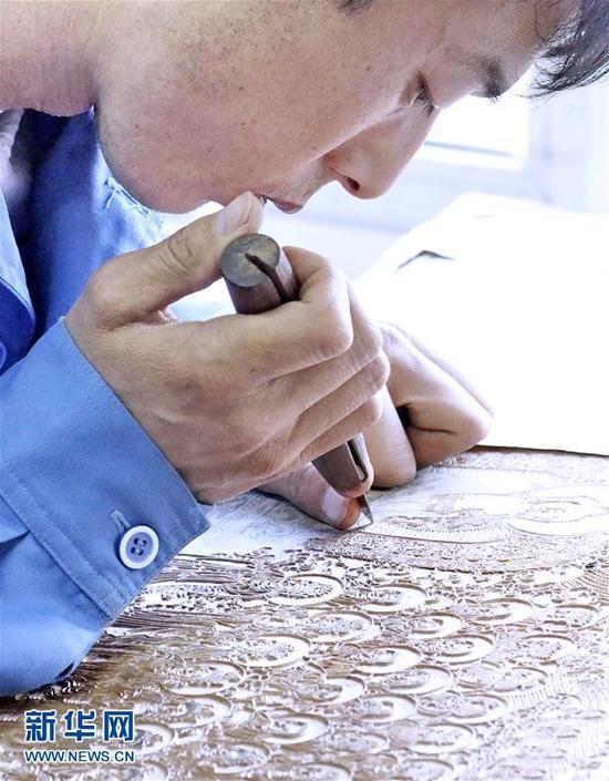 1月6日,雕版技师在对照原版的《清敕修大藏经》扫描文件补刻经板。