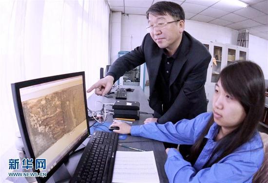1月6日,技术人员和专家在对木雕经板进行堪对和数字化处理。