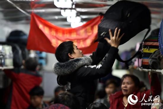 1月13日,旅客上车后摆放行李。(人民网记者 翁奇羽 摄)